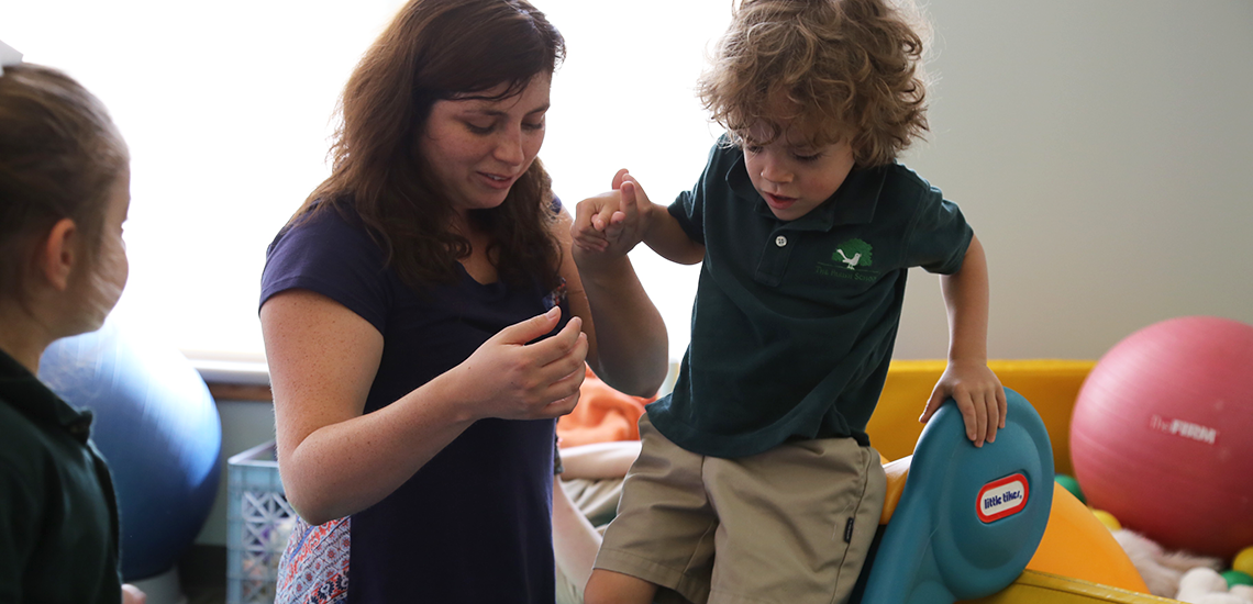 Physical Therapist helps child at The Carruth Center